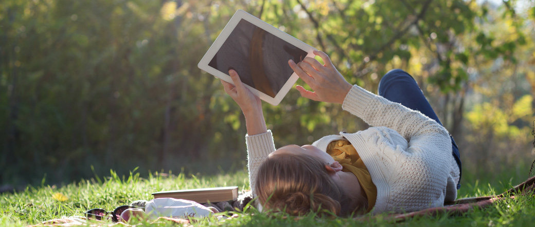 Woman Lying On Bedding On Green Grass With Ipad During Picknic I